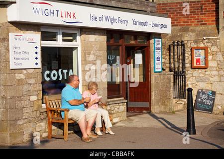 Pareja adulta se sentó en banco disfrutando de helados fuera de la terminal de ferry de Wightlink en Yarmouth, Isla de Wight, Hampshire, Reino Unido en septiembre Foto de stock