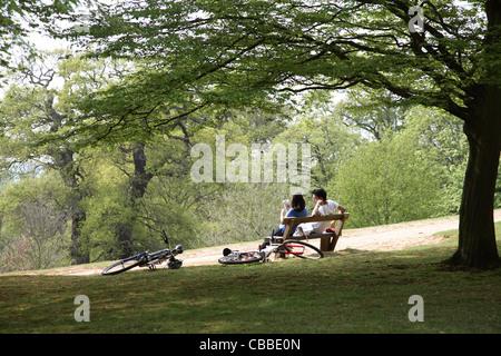 Una joven pareja relajarse sentados en un banco en la cima de la colina de Richmond Park de Londres. Sus bicicletas apoyadas en el suelo junto a ellos.