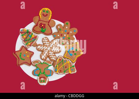 Colorido gingerbread cookies en una placa blanca contra el fondo rojo.