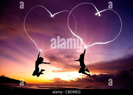 Pareja joven saltando y dibujo corazones conectados por una linterna en el aire en la playa antes de amanecer Foto de stock
