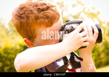 Un muchacho de 7 años, utilizando una cámara digital SLR en un soleado jardín. Foto de stock