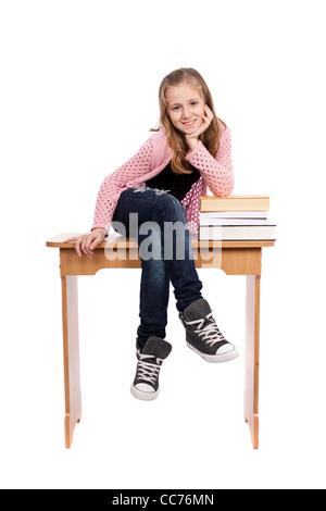 Lindo rubia colegiala sentado en su escritorio con un montón de libros cercano