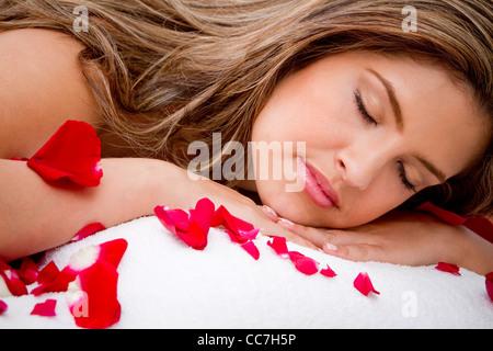 La mujer hispana poniendo en camilla de masaje, cubierto de pétalos de rosa