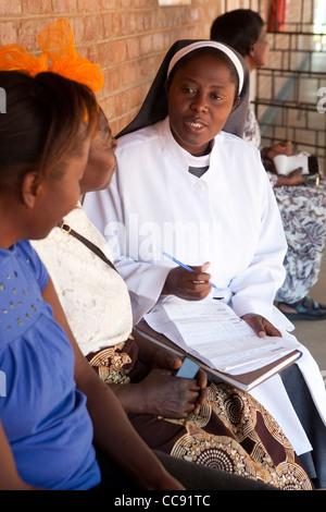 Un profesional de la salud asesora a los pacientes a un hospital católico romano en Ibenga, Zambia, África del Sur.