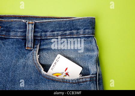 Naipes Joker en el bolsillo de los pantalones vaqueros azules con fondo verde Foto de stock