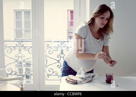 A mediados de mujer adulta esparcir mermelada en las tostadas Foto de stock