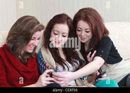 Tres de generación z amigos una adolescente de 15 años tener una risa viendo fotos en un teléfono móvil mientras estábamos sentados en un sofá juntos. UK