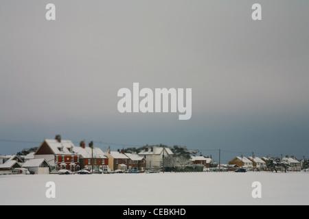Escenas de nieve de Kent, el paisaje a través de un campo nevado a una fila de casas.