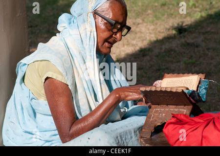 Viuda la lectura de un libro religioso, Ma Dham Ashram, dirigidos por ONG Guild of Service, Vrindavan, Uttar Pradesh, India