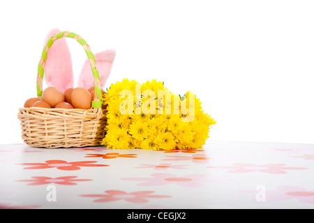 Canasta de Pascua con huevos, flores amarillas y orejas de conejo rosa, aislado sobre fondo blanco.