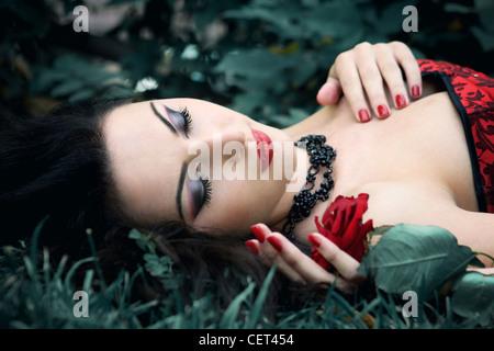 Mujer joven con cabello oscuro vistiendo vestido rojo acostada sobre su espalda al aire libre celebrar una sola subió con los ojos cerrados Foto de stock