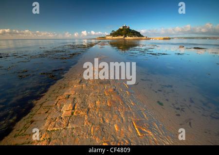 Amanecer sobre la antigua calzada de piedra artificial hacia St Michaels Mount frente a la costa de Cornualles.