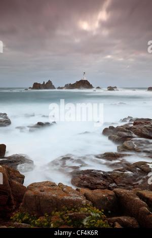 El mar embravecido alrededor de la Corbiere Lighthouse al atardecer. El faro fue el primero en las Islas Británicas para ser construido de hormigón.