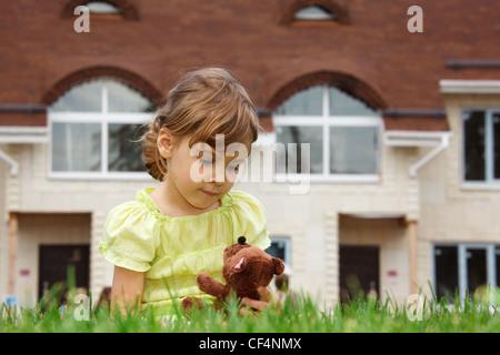 Niña sentada en el césped delante de la casa nueva. En sus manos sostiene juguete osito de peluche.