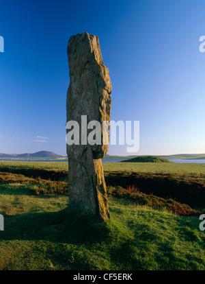 Mirando desde la estatura losa occidental del anillo de Brodgar Stone Circle, a través del lago de Stenness Ward Hill en la isla o