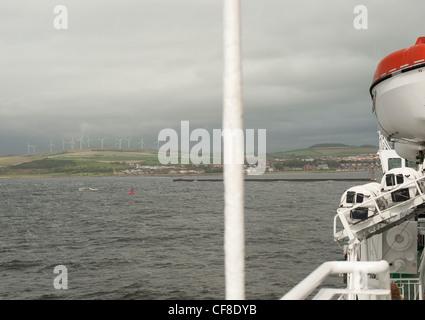 Vista al mar desde un ferry con cubierta de bote de rescate en primer plano y el parque eólico en el horizonte en la distancia en Escocia
