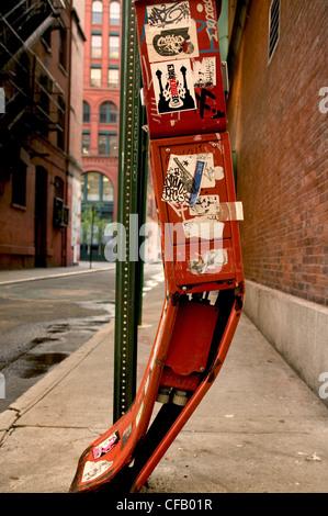 Cuadro de letra roja doblada que está cubierto de pegatinas y graffiti en NYC.