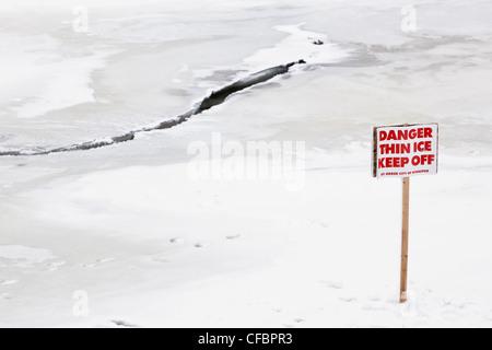 Peligro de una fina capa de hielo se mantengan fuera de la señal de advertencia. Río Rojo, en Winnipeg, Manitoba, Canadá.
