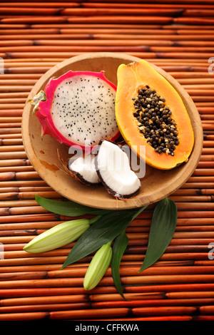 Dragon fruit, papaya y coco en el tazón de madera sobre fondo de bambú