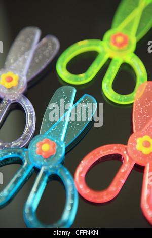 Las tijeras infantiles de colores brillantes sobre fondo negro Foto de stock