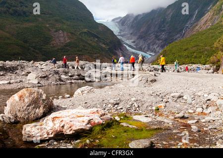 Los turistas que cruzan un puente cerca del glaciar Franz Josef, Costa oeste, Nueva Zelanda.