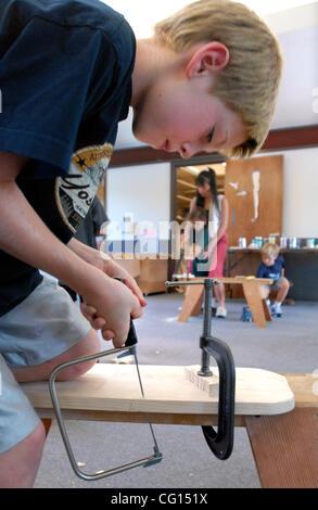 Independiente--Eric Mortl, 8, se desprende que el aserrín como él corta una guitarra forma utilizando una sierra caladora durante la clase de carpintería para niños Martes, 24 de julio de 2007, en Walnut Creek, California, en el fondo de cristal Jeab ayuda a un estudiante con un corte de sierra. La clase se ofrece a través de la Walnut Creek parques y recr