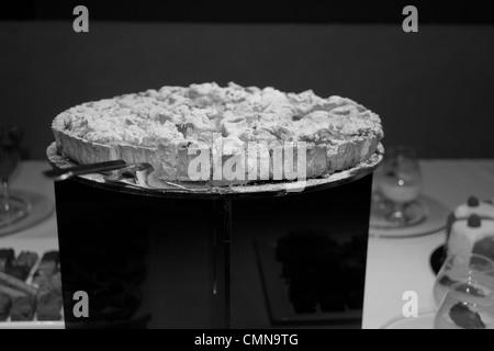 En una fiesta corporativa en Londres, un pastel dulce casero sobre un pedestal con un cortador circular/servidor; otros postres son en el fondo