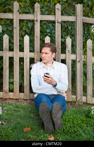 Hombre apoyado en valla con un teléfono celular en la mano Foto de stock
