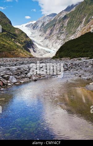 El glaciar Franz Josef, Costa oeste, Nueva Zelanda, reflejada en un arroyo en el valle.