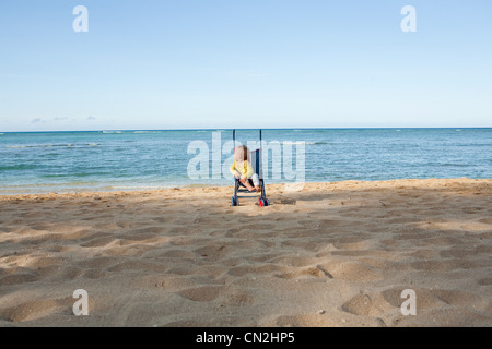 Cochecito de niño en niño en la playa