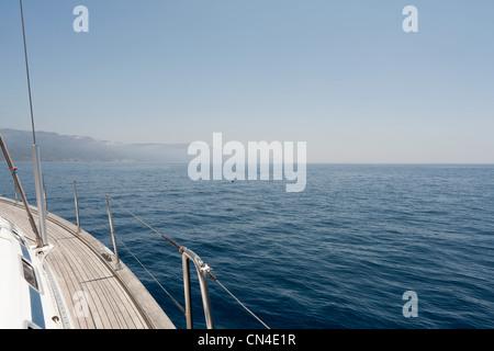 Vista del lado de un yate y la costa de Cerdeña