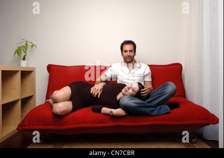 Pareja joven sentado en un sofá rojo