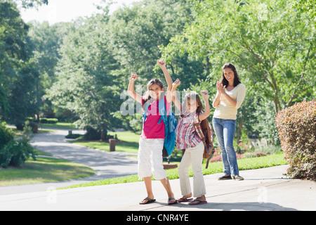 Madre y sus hijas caminando a casa de la escuela