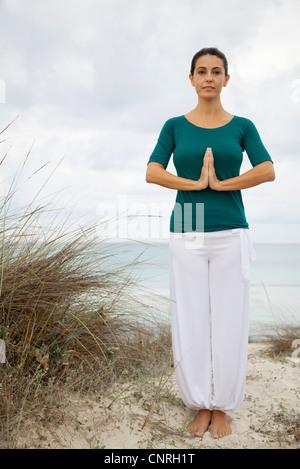 Mujer madura en posición de oración de yoga en la playa, Retrato