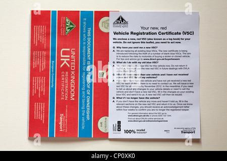 Nuevo certificado de registro de vehículo rojo V5C con carta documento aislado sobre fondo blanco.