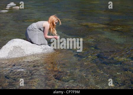 Mujer joven sentada sobre una roca en un río y bebe el agua de las manos