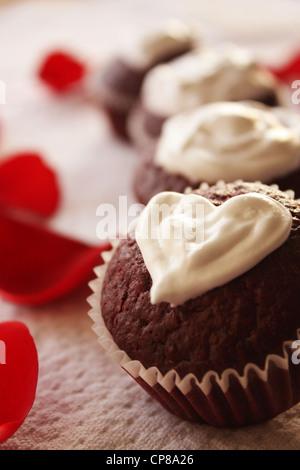 El día de San Valentín temáticas pastelitos de terciopelo rojo con forma de corazón topping de queso crema. Los pétalos de rosa son vistos en el fondo Foto de stock