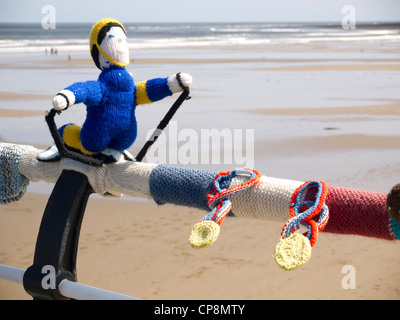 Bombardeo de hilados decorar lugares públicos con objetos tejidos Olímpico aquí un esquiador Olímpico en Saltburn pier pasamanos