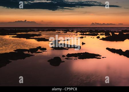 Puesta de sol en el Pacífico con rocas de lava en primer plano.
