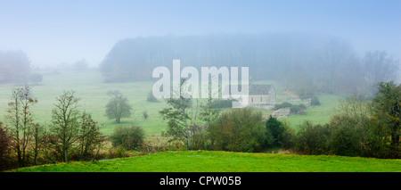 Misty escena y la iglesia de St Oswald, una capilla remota en un campo, en Widford cerca de Burford en Cotswolds, Oxfordshire, REINO UNIDO