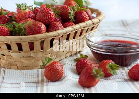 Mermelada de Fresa en un recipiente transparente y las fresas maduras en una caja de madera