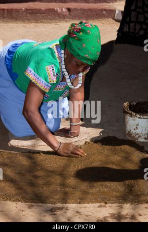 Mujer africana tradicional propagación de barro y arcilla en el suelo