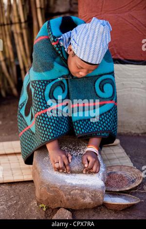 Una mujer africana tradicional de moler el trigo en una roca