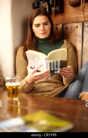 Mujer leyendo con cerveza en el pub