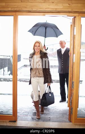 Par de caminar a través de las puertas delanteras del hotel Foto de stock