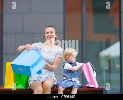 La madre y el niño examina las compras después de las compras Foto de stock