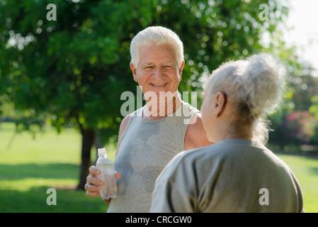 Personas Mayores, el viejo hombre y mujer hablando y bebiendo el agua después de hacer ejercicio en el parque
