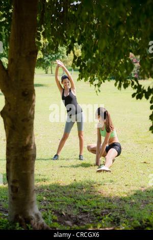 Dos mujeres hermosas estiramiento en el parque de la ciudad y después de ejecutar la actividad deportiva