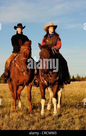 Vaquero y cowgirl montando caballos, mirando a la distancia, Saskatchewan, Canadá, Norteamérica Foto de stock