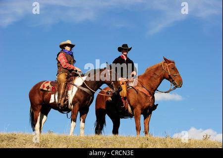 Cowgirl y cowboy a caballo mirando a la distancia, Saskatchewan, Canadá, Norteamérica Foto de stock